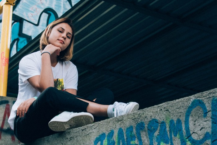 Portrait of a teenage female sitting on a ledge with grafitti.